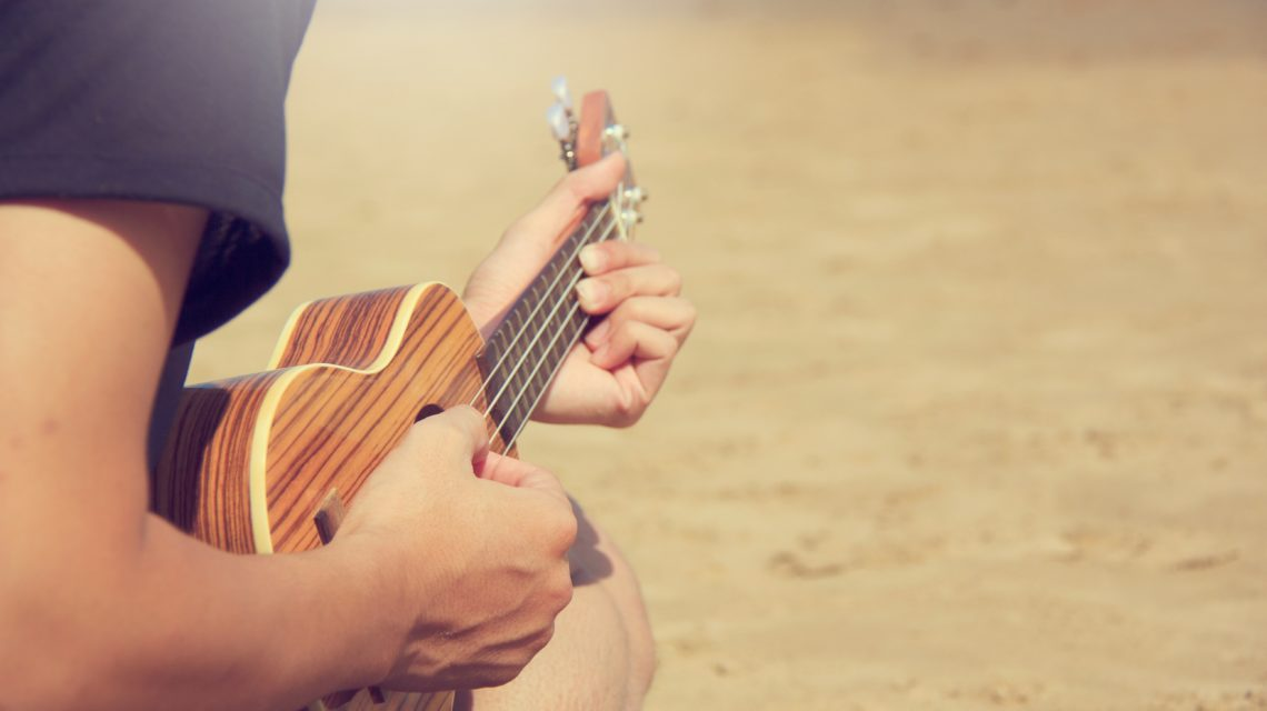adult male playing music on beach