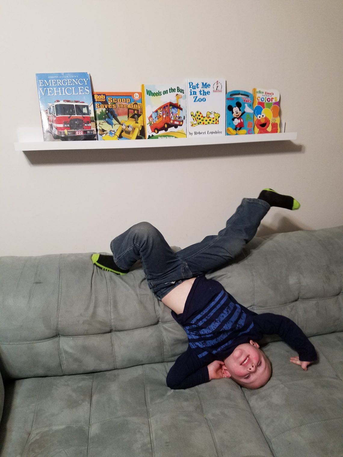 four year old boy doing headstand on couch